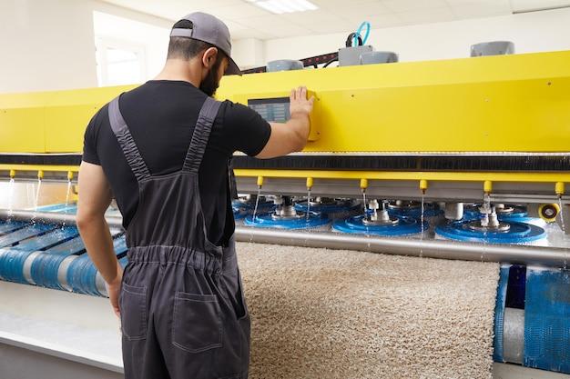 Mężczyzna obsługujący pralkę automatyczną do dywanów w profesjonalnej pralni