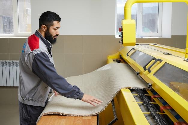 Mężczyzna obsługujący pralkę automatyczną do dywanów w profesjonalnym serwisie sprzątającym