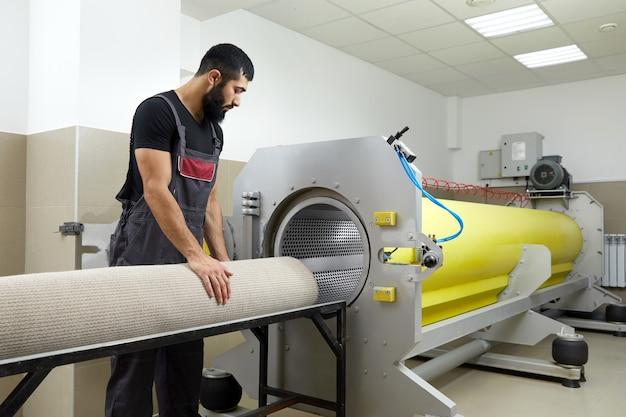 Mężczyzna obsługujący suszarkę do czyszczenia dywanów. profesjonalna usługa czyszczenia dywanów