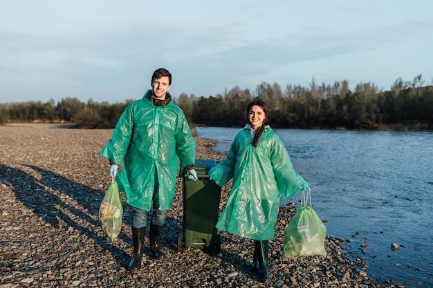 Mężczyzna ochotnik z dziewczyną zdjąć śmieci na plaży. zanieczyszczenie środowiska wybrzeża, śmieci na zewnątrz i śmieci.