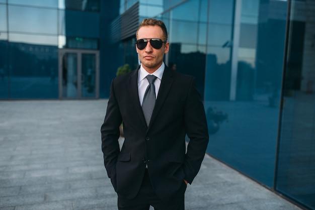 Mężczyzna ochroniarz w garniturze i okularach przeciwsłonecznych na zewnątrz. ochrona to ryzykowny zawód.