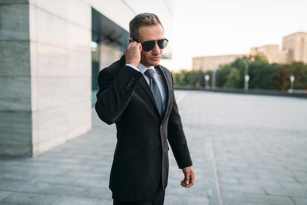 Mężczyzna ochroniarz w garniturze i okularach przeciwsłonecznych rozmawia przez słuchawkę ochronną na zewnątrz. profesjonalna ochrona to ryzykowny zawód