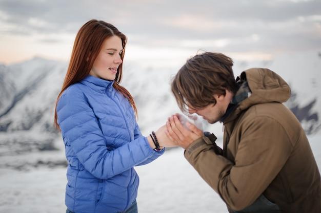 Mężczyzna ocieplenie jego ręce dziewczyny z oddychaniem w górach
