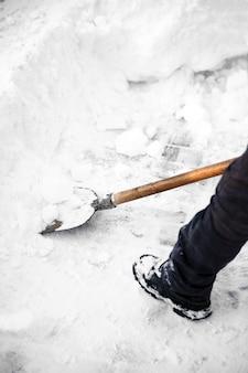 Mężczyzna oczyszcza ulicę ze śniegu