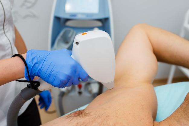 Mężczyzna odbiera laserową depilację pod pachą w centrum urody