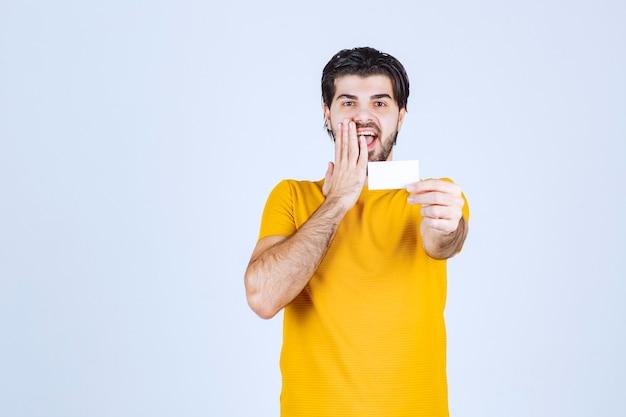 Mężczyzna odbiera wizytówkę partnera i jest zaskoczony.