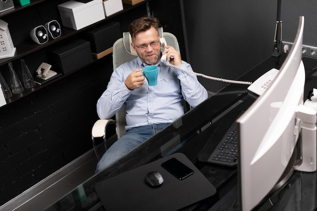 Mężczyzna odchylił się na krześle, pijąc kawę i rozmawiając przez telefon stacjonarny