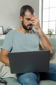 Mężczyzna odczuwa ból oczu podczas pracy na laptopie w domu