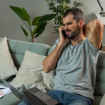 Mężczyzna odczuwający ból szyi podczas pracy na laptopie w domu
