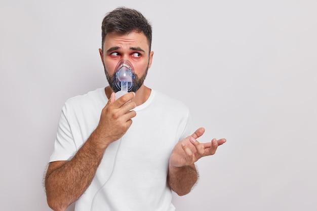 Mężczyzna oddycha przez maskę nebulizatora sprawia, że procedury terapeutyczne leczą choroby układu oddechowego lub alergię cierpi na astmę, wzrusza ramionami i wygląda na nieświadomego odizolowanego na białej ścianie studia