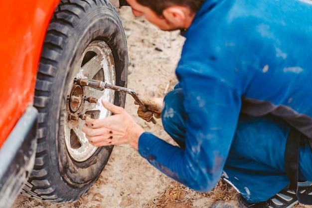 Mężczyzna odkręca śruby na kole