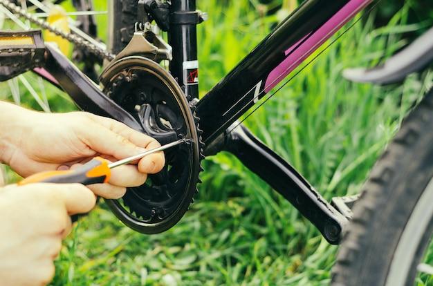Mężczyzna odkręca śruby pomarańczowym śrubokrętem na łańcuchu rowerów górskich na tle trawy. naprawa na leśnej drodze.
