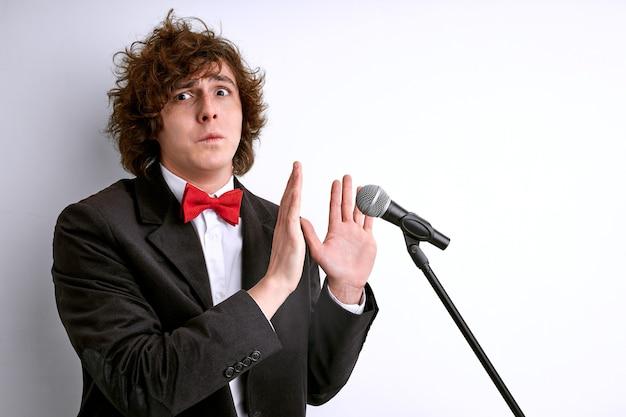 Mężczyzna odmawia mówienia, nie trzeba mówić, wstydź się przy mikrofonie. pojedynczo na białej ścianie
