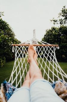 Mężczyzna odpoczywa leżąc na hamaku w tropikalnym ogrodzie. koncepcja podróży i wakacji.