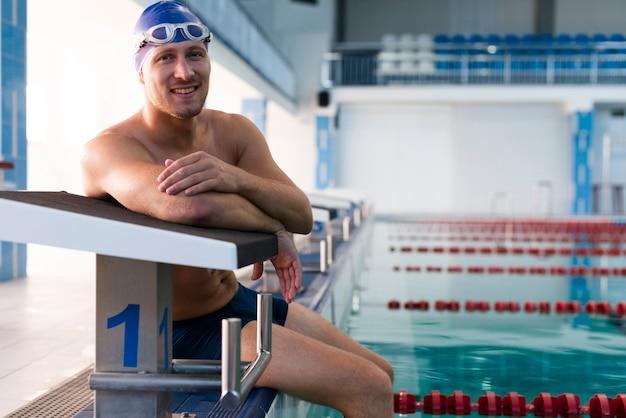 Mężczyzna odpoczywa na krawędzi pływackiego basenu