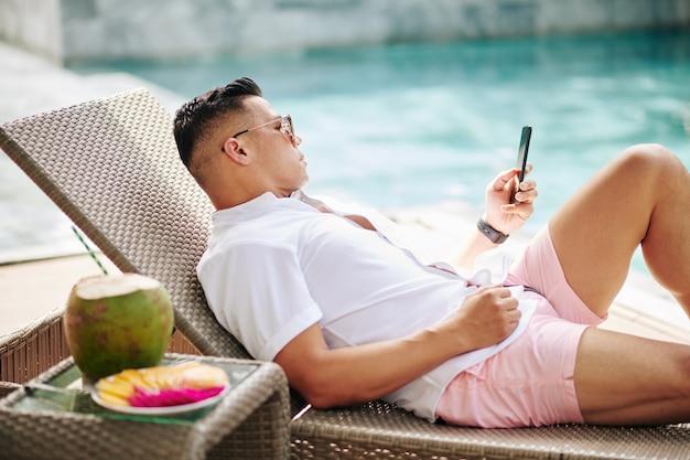 Mężczyzna odpoczywa na szezlongu przy basenie i czyta wiadomości tekstowe lub sprawdza powiadomienia na smartfonie