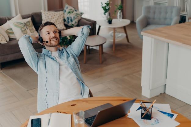 Mężczyzna odpoczywa po ciężkim dniu pracy trzyma ręce za głową myśli o czymś i planuje siedzi przy biurku z laptopem notatnik słucha audio kurs biznesowy przez słuchawki działa zdalnie