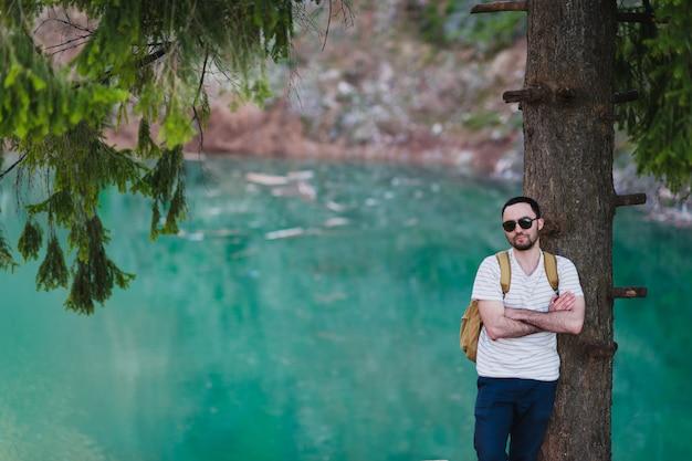 Mężczyzna odpoczywa przeciw drzewu jeziorem z plecakiem