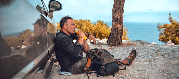 Mężczyzna odpoczywa samochodem i pije sok pomarańczowy
