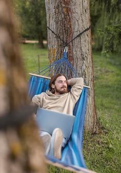Mężczyzna odpoczywa w hamaku z laptopem