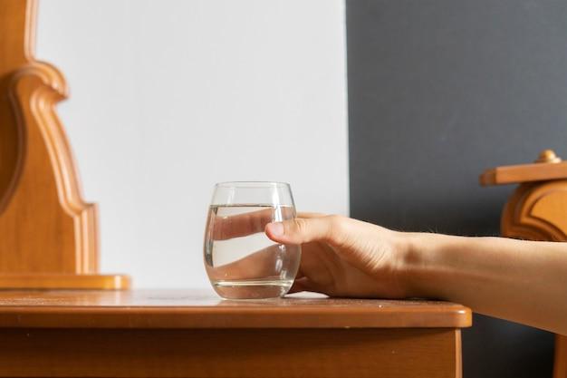 Mężczyzna odpoczywa w łóżku i dostaje szklankę wody. koncepcja pragnienie b