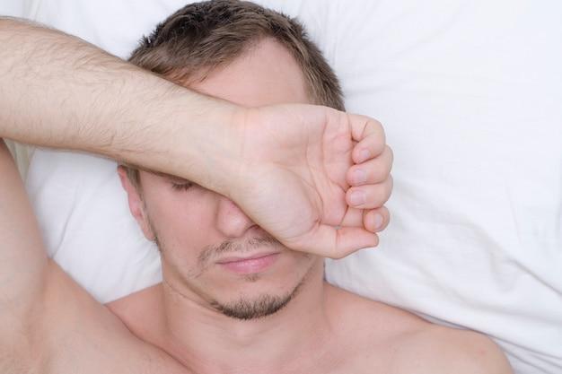 Mężczyzna odpoczywa w masce dla snu. zarost na jego twarzy.