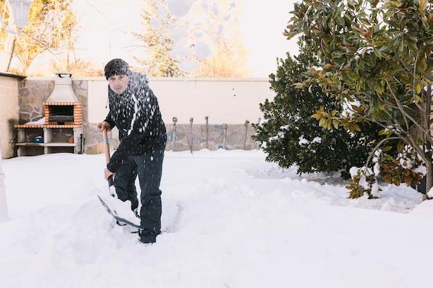Mężczyzna odśnieżający ogród swojego domu łopatą