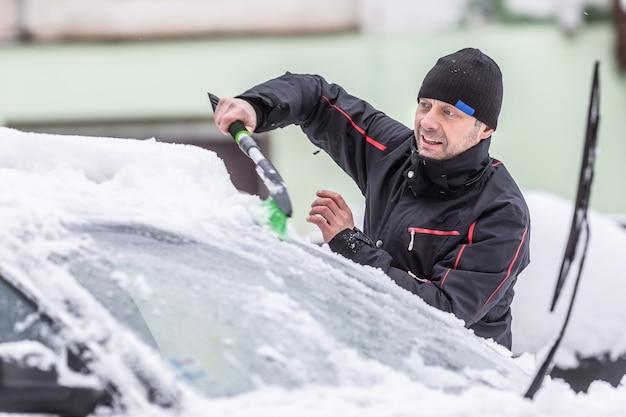 Mężczyzna odśnieżający z samochodu zaparkowanego na zewnątrz po obfitych opadach śniegu w nocy.