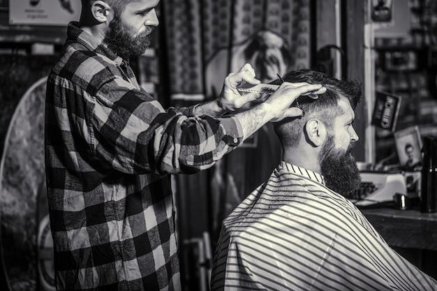 Mężczyzna odwiedzający fryzjera w salonie fryzjerskim. nożyczki fryzjerskie. czarny i biały. brodaty mężczyzna w sklepie fryzjerskim.