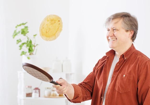 Mężczyzna odwraca naleśnik w powietrzu w kuchni