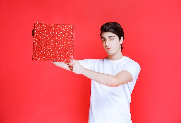 Mężczyzna oferujący czerwone pudełko w walentynki