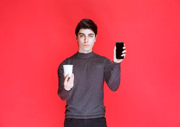 Mężczyzna oferujący partnerowi białą filiżankę kawy