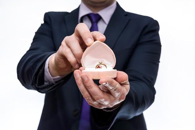Mężczyzna oferujący pierścionek z brylantem w pudełku prezentowym