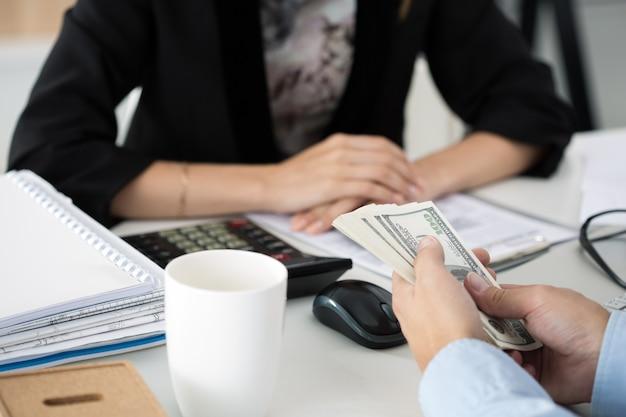 Mężczyzna oferuje partię banknotów stu dolarowych. ręce z bliska. venality, łapówka, pojęcie korupcji