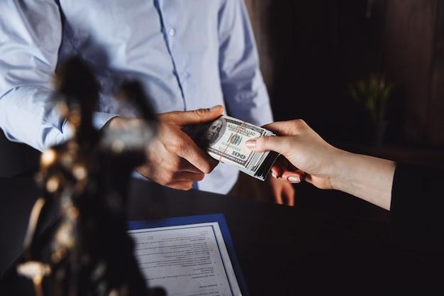 Mężczyzna oferuje partię banknotów stu dolarowych. ręce z bliska