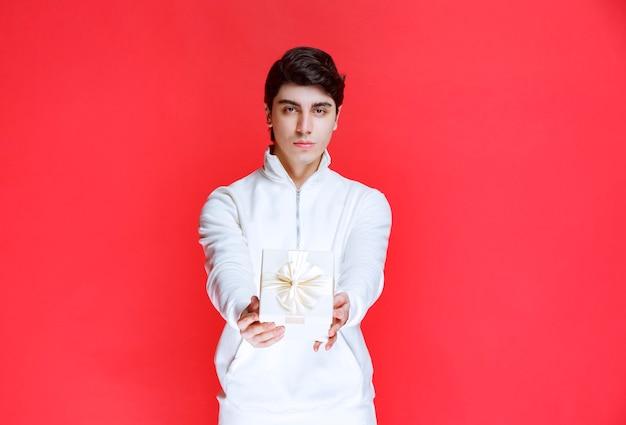 Mężczyzna oferuje swojemu partnerowi białe pudełko prezentowe.