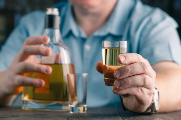 Mężczyzna oferuje whisky. elegancki mężczyzna trzyma i trzyma kieliszek
