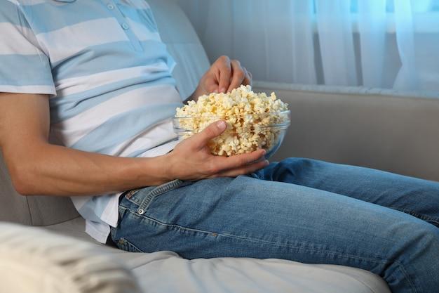 Mężczyzna ogląda film na kanapie i je popcorn. jedzenie do oglądania filmów