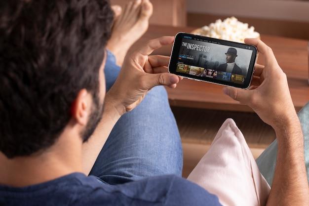 Mężczyzna ogląda netfliksa na swoim telefonie