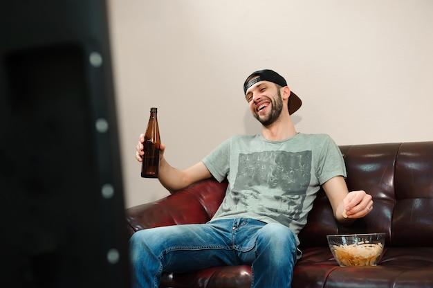 Mężczyzna ogląda piłkę nożną, fan piłki nożnej na kanapie.