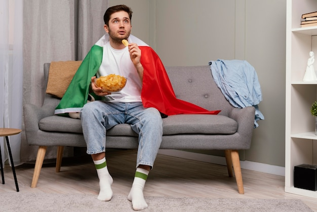 Mężczyzna ogląda program sportowy w telewizji