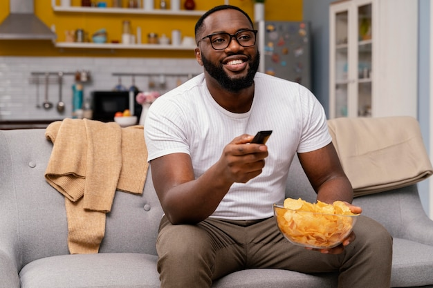 Mężczyzna ogląda telewizję i je frytki