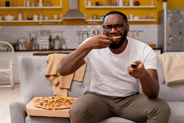 Mężczyzna ogląda telewizję i je pizzę