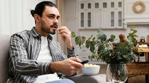 Mężczyzna ogląda telewizję i je popcorn