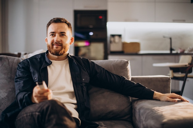 Mężczyzna ogląda telewizję w domu i siedzi sofa
