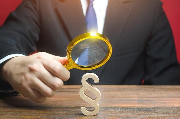 Mężczyzna ogląda za pomocą szkła powiększającego figurkę z paragrafu, stanowienie prawa i prawodawstwo