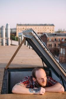 Mężczyzna ogląda zachód słońca na dachu. kreatywny wypoczynek. artystyczny nastrój, romantyczna randka, młody stylowy hipster z naciskiem na pierwszy plan, koncepcja miejska