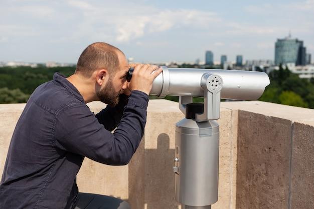 Mężczyzna oglądający przez teleskop lornetki