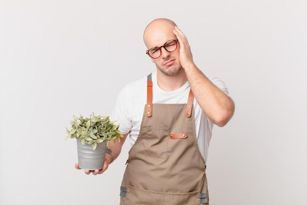 Mężczyzna ogrodnik czuje się znudzony, sfrustrowany i senny po męczącym, nudnym i żmudnym zadaniu, trzymając twarz dłonią