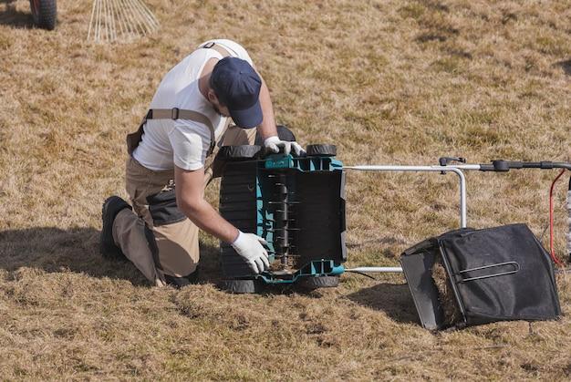 Mężczyzna ogrodnik czyszczenia wertykulatora maszyny ze starej suchej trawy na trawniku